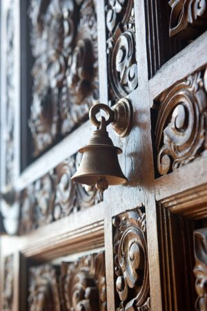 door bell: Old brass bell on an ornately carved door embellished with a swirling handcrafted pattern viewed at an oblique angle with incoming light Stock Photo