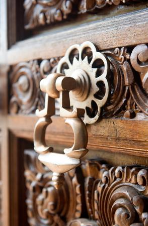 foliate: Ornate bronze door handle or knocker on an intricately carved wooden panel with floral and foliate motifs viewed at an oblique close up angle