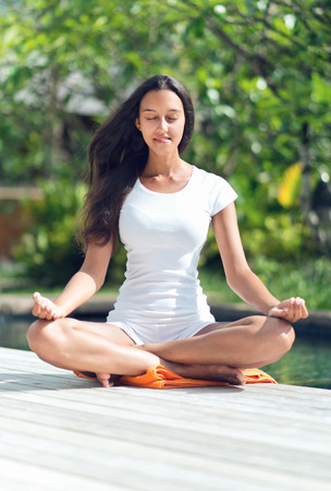 Close up Pretty Young Woman with Long Black Hair Doing Lotus Yoga at the Poolside With Closed Eyes photo