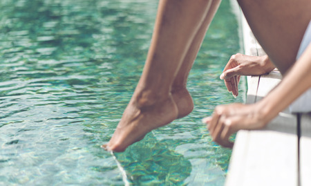 Close up Young Woman Relaxing at the Poolside with Toes on Beautiful Clear Water