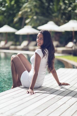 Smiling Indian Woman in White Shirt and Shorts with Long Black Hair Relaxing at the Poolside While Looking at the Camera. photo