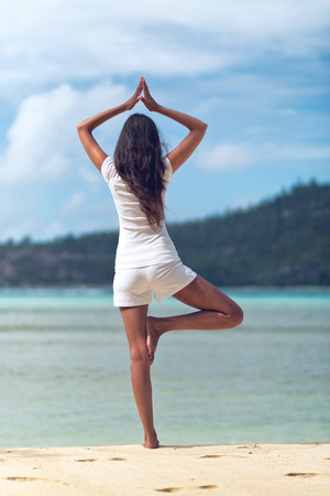 Rear View of Long Hair Woman Doing Yoga Activity at the Beach, Performing One Leg Balance with Hands Above the Head. photo