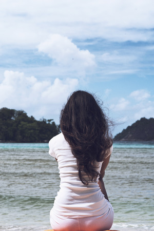 Close up Slim Woman with Long Wavy Black Hair Sitting on the Sand in Front Beautiful Beach on a Sunny Day. Stock Photo