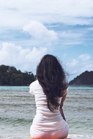 černé vlasy: Zblízka štíhlá žena s dlouhými vlnitými vlasy, sedí na černé písku v titulní krásné pláži za slunečného dne.
