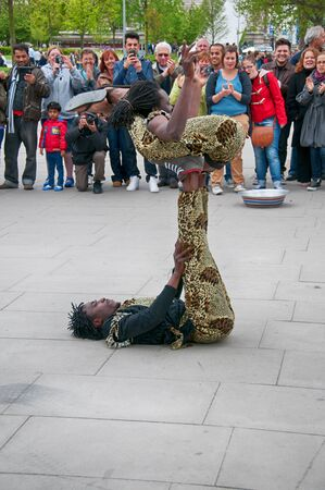 contortionist: Group of Jamaican street performers and acrobats giving a performance for a group of people at Southbank, London, England Editorial