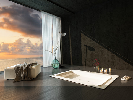 fittings: Romantic sunken bathtub in a dark accented modern bathroom with parquet floor and panoramic view window at sunset with candles and clothes draped on an ottoman