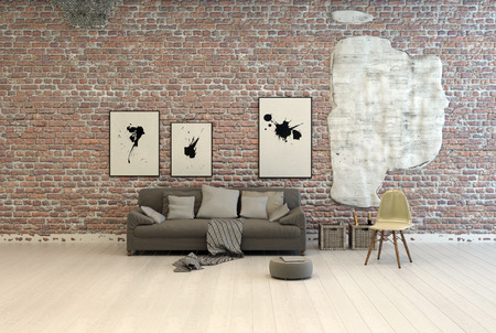 Generic grey sofa with comfortable cushions and footstool against a brick wall with abstract artwork in a large light room with white painted wooden floorboards Stock Photo