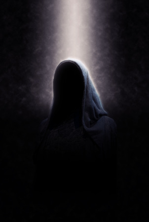 Eerie Image of Creepy Dimly Lit Faceless Cloaked Figure in Spotlight on Dark Background Stock Photo
