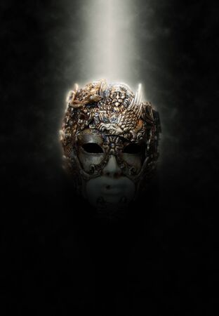 concealed: Ornate and Intricately Carved Mask Illuminated from Above by Bright Spotlight on Dark Background