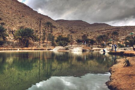 muscat: Storm Clouds over Wadi Bani Khalid Surrounded by Palm Trees and Hills, outside of Muscat, Oman Stock Photo
