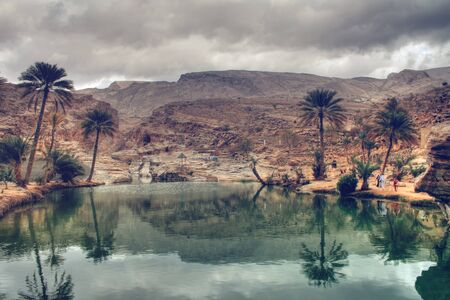 oasis: Dark Grey Storm Clouds Reflected in Water of Wadi Bani Khalid Surrounded by Hills and Palm Trees, outside of Muscat, Oman
