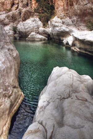 bani: Overview of Green Water of Wadi Bani Khalid with Boulders and Rocky Cliffs Outside of Muscat, Oman Stock Photo