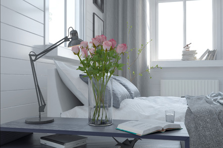 Pretty vase of fresh pink roses in a modern bedroom interior standing alongside an anglepoise lamp on the bedside table