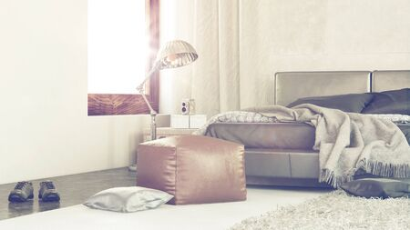 pouffe: Bright sunny modern bedroom interior with sun flare from a large window and a close up corner view of a rumpled bed, leather pouffe and shoes on the floor Stock Photo
