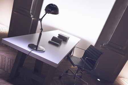 tilted view: Interior of a corporate directors office with an uncluttered long desk, anglepoise lamp and office chair with architectural pillar detail, tilted angle close up view Stock Photo