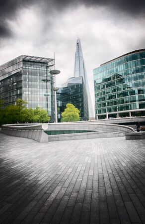 shard of glass: View of the Shard amongst modern glass fronted office blocks and urban exterior architecture in London, England Stock Photo