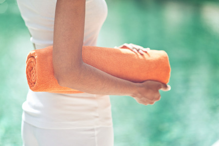 wellness: Close up torso view of a slender young woman standing poolside with a rolled towel against sparkling cool blue water Stock Photo