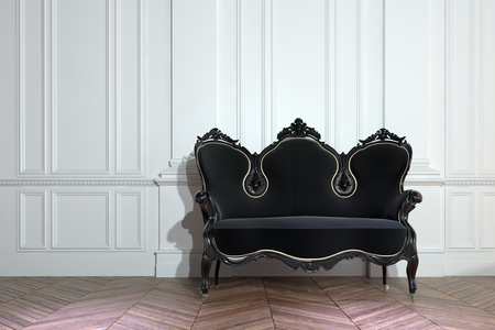Black vintage ornately carved wooden couch against a white paneled wall on a bare parquet floor with herringbone pattern in a class house interior