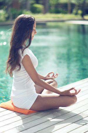 mujer meditando: Close up Tan mujer joven con el pelo largo Negro hace yoga en el lado de la piscina para estar física y mentalmente sanos. Capturado en vista lateral. Foto de archivo