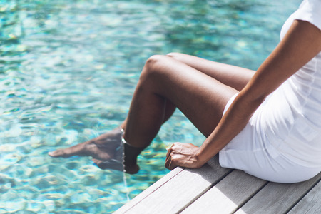 woman barefoot: Close up Asian Indian Woman in White Casual Outfit Resting at Poolside with Both Feet on Clear Water