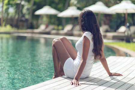 resort: Long Hair Slim Asian Indian Woman Unwinding at Poolside on One Sunny Day.