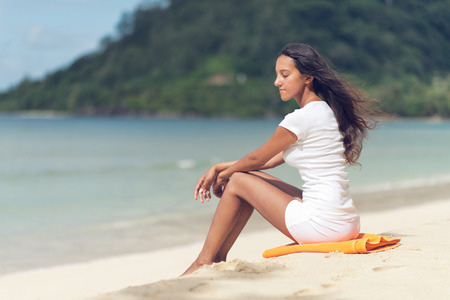 unwinding: Young Indian Woman Unwinding at the Beautiful Beach with Closed Eyes while Day Dreaming.
