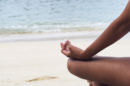Close up Hand Gesture Indian Woman Performing Yoga at the Beachfront on a Sunny Day. photo