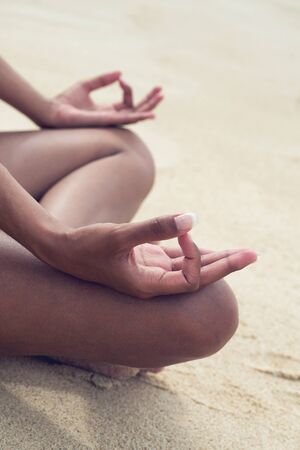 Close up Hand Gesture on Knees of Asian Indian Woman Doing Lotus Yoga on Beach Side. photo