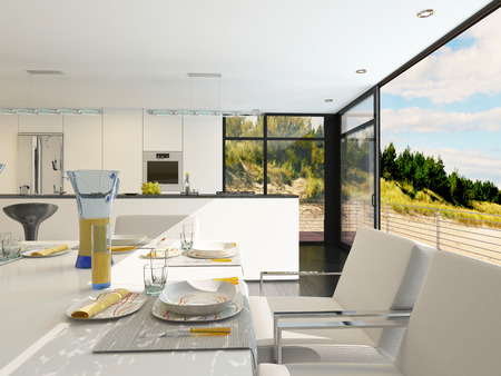 Modern open-plan dining area with stylish place settings on a contemporary table with metal framed upholstered chairs, panoramic view windows and a kitchen area with fitted appliances photo