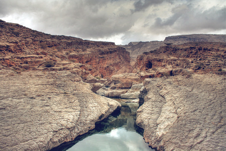 Scenic of Wadi Bani Khalid Running Through Rocky Canyon with Dark Grey Storm Clouds Overhead, outside of Muscat, Oman photo