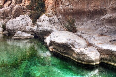 bani: Detail of Emerald Green Water in Wadi Bani Khalid with Large Boulders, outside of Muscat, Oman