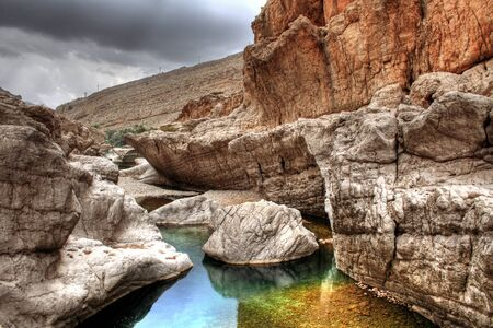 Wadi: Colorful rocks in a tranquil rock pool in Wadi Bani Khalid near Muscat, Oman Stock Photo