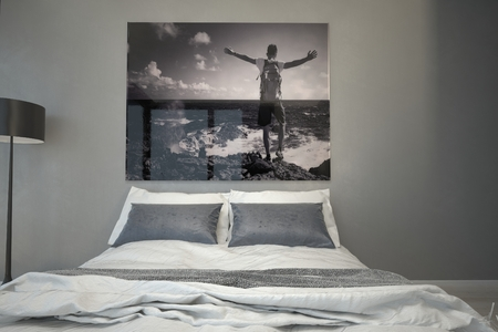 artwork: Man at the Sea Artwork Hanging on a Gray Wall Inside an Architectural Bedroom with White and Gray Bed.