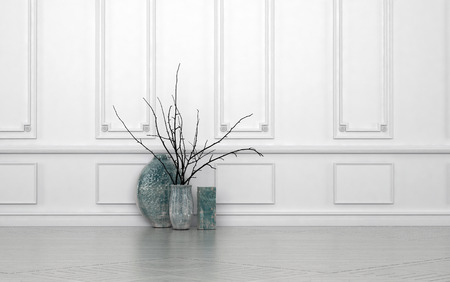 Modern arrangement of twigs in hand crafted ceramic vases of different shapes standing on the floor against a white paneled wall with copyspace Stock Photo