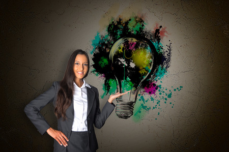 motioning: Smiling Businesswoman Standing with Hand on Hip and Motioning with Other Toward Abstract Lightbulb Graphic on Wall, Business Idea Concept