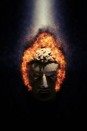 intimidating: Detail of Old Stone Buddha Head on Fire Dramatically Lit from Above on Dark Background, Meditation and Spirituality Concept Still Life Image Stock Photo