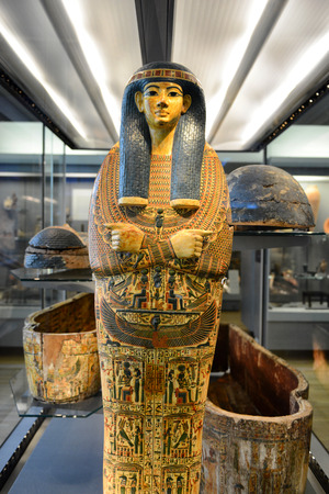 Egyptian Pharaoh Mummy Coffin Shrine Decorated in Ornate Hieroglyphics Standing Amongst Open Coffins in Museum Display Redactioneel