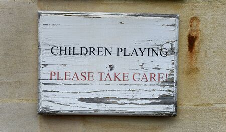 vicinity: Children Playing - Please Take Care rustic wooden signboard with peeling paint mounted on a wall warning of children in the vicinity