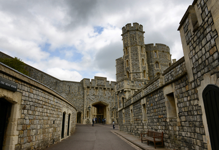curfew: Historical medieval stone buildings, Windsor Castle, Berkshire, UK in the Lower Ward of the Castle with a walkway leading to an arched entrance and crenelated tower behind