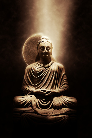 lit image: Dramatically Lit Sepia Colored Image of Stone Sitting Buddha Statue, a Diety Symbol of Buddhist Religion, Isolated on Dark Background