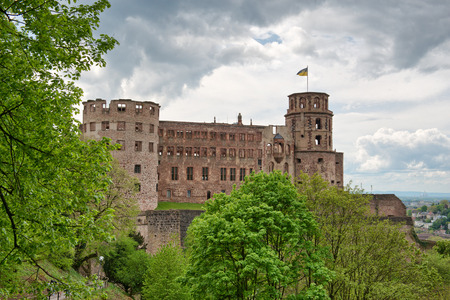 roofless: Green vegetation in front of the ruins of Heidelberg Castle, historical tourist attraction, under a dramatic cloudy sky, in Germany