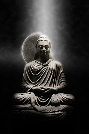 stone buddha: Full Length Stone Carved Seated Buddha Statue Dramatically Lit from Above on Dark Background, Meditation and Spirituality Concept Still Life Image