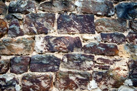 weatherworn: Background texture of a natural rock wall with roughly hewn rectangular bricks with rough weathered surfaces, full frame