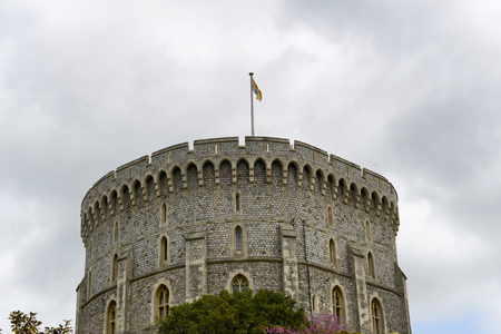 View of the Round Tower, Windsor Castle, Berkshire, UK, or original fortified medieval keep on its motte, viewed over a stone wall against a cloudy sky