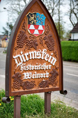 city coat of arms: City name place sign for Dirmstein, Germany decorated with a coat of arms and bunches of grapes depicting its status as a wine town on the scenic wine route through the region