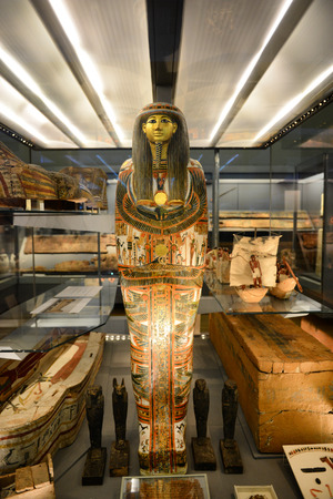 life after death: Egyptian Pharaoh Mummy Coffin Shrine Decorated in Ornate Hieroglyphics Standing Amongst Open Coffins in Museum Display Editorial