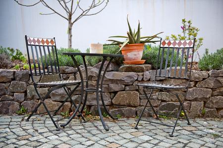 empedrado: Mesa de hierro forjado Libre y sillas en un patio al aire libre de pie en la pavimentación junto a un jardín de rocas amurallada con un cactus en maceta en la pared Foto de archivo