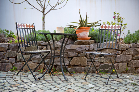 Vacant wrought iron table and chairs on an outdoor patio standing on paving alongside a walled rock garden with a potted cactus on the wall