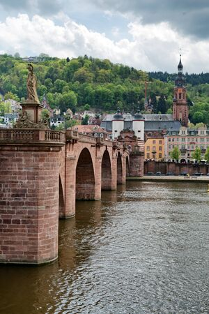old bridge: Looking Across Neckar River at Old Bridge Leading to Old Town Heidelberg, Baden-Wurttemberg, Germany with Clouds Overhead Stock Photo