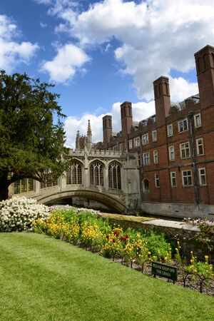 punting: View from the lawns in the court of St Johns College of the elegant historical Bridge of Sighs, Cambridge, England spanning the River Cam with colorful spring flowers in the foreground Editorial